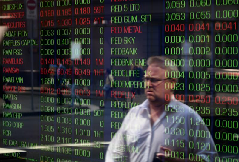 A passerby is reflected in the window of the Sydney Stock Exchange showing the benchmark S&P/ASX200 index in Sydney on September 18, 2015. Australian stocks slipped 0.28 percent at the open after the US Federal Reserve left interest rates near zero overnight. AFP PHOTO / Peter PARKS (Photo credit should read PETER PARKS/AFP via Getty Images)