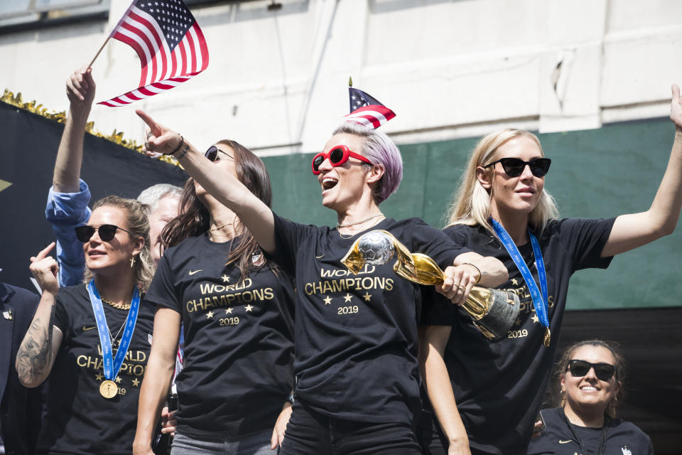 MANHATTAN, NY - JULY 10: Megan Rapinoe #15 of United States points to the crowds as she holds the 2019 FIFA World Cup Champion Trophy, Ashlyn Harris #18 of United States Alex Morgan #13 of United States and Allie Long #20 of United States ride on the World Champions float as it rides down Broadway for the Ticker Tape through the Canyon of Heroes.  This celebration was put on by the City of Manhattan to honor the team winning the 2019 FIFA World Cup Championship title, their fourth, played in France against Netherlands, at the City Hall Ceremony in the Manhattan borough of New York on July 10, 2019, USA.  (Photo by Ira L. Black/Corbis via Getty Images)