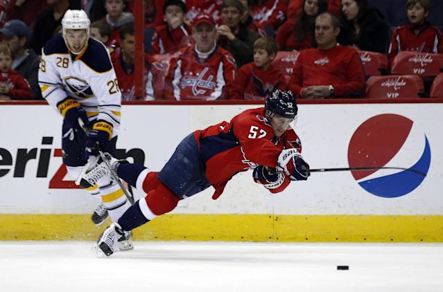 Washington Capitals defenseman Mike Green (52) falls in front Buffalo Sabres center Zemgus Girgensons (28), from Latvia, in the second period of an NHL hockey game, Sunday, Jan. 12, 2014, in Washington. (AP Photo/Alex Brandon)