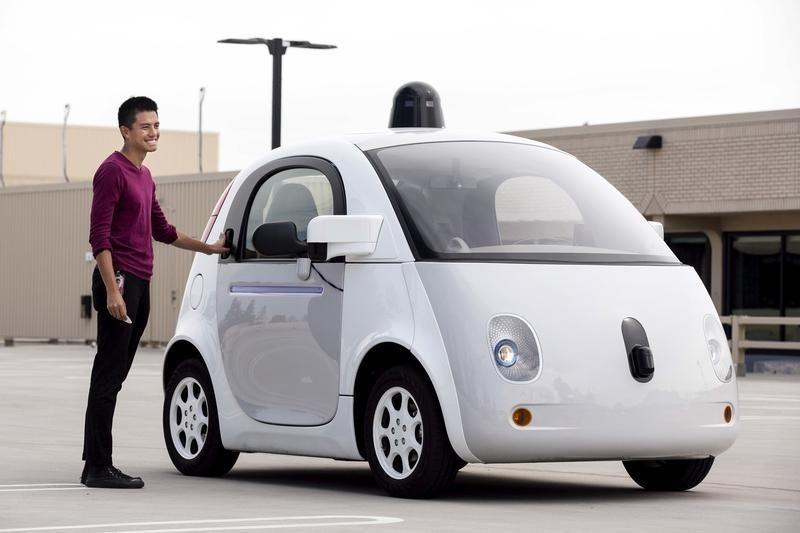 Google vehicle operator Reko Ong stands next to a prototype of Google's own self-driving vehicle during a media preview of Google's current autonomous vehicles in Mountain View, California