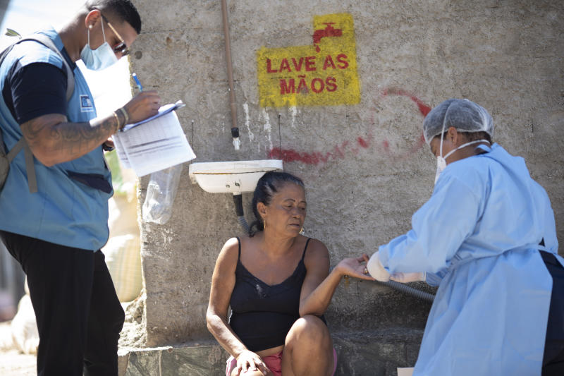 A woman gets tested with a quick COVID-19 test during a city new program that aims to administer 20 thousand tests in Rio de Janeiro's poor neighborhoods, at Morro da Providencia favela, Rio de Janeiro, Brazil, Thursday, Sept. 3, 2020. (AP Photo/Silvia Izquierdo)
