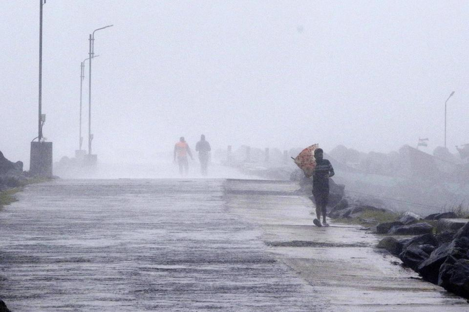A man tries to hold his umbrella against strong winds at the Kasimedu Harbor on the Bay of Bengal coast in Chennai, India, Wednesday, Nov.25, 2020. India's southern state of Tamil Nadu is bracing for Cyclone Nivar that is expected to make landfall on Wednesday. The state authorities have issued an alert and asked people living in low-lying and flood-prone areas to move to safer places. (AP Photo/R. Parthibhan)