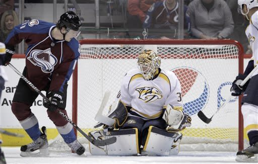 The puck gets past Nashville Predators goalie Chris Mason (30) for a goal by Colorado Avalanche defenseman Tyson Barrie (41), not shown, as Colorado Avalanche left wing Jamie McGinn (11) watches during the first period of an NHL hockey game, Monday, Feb. 18, 2013, in Denver.(AP Photo/Joe Mahoney)
