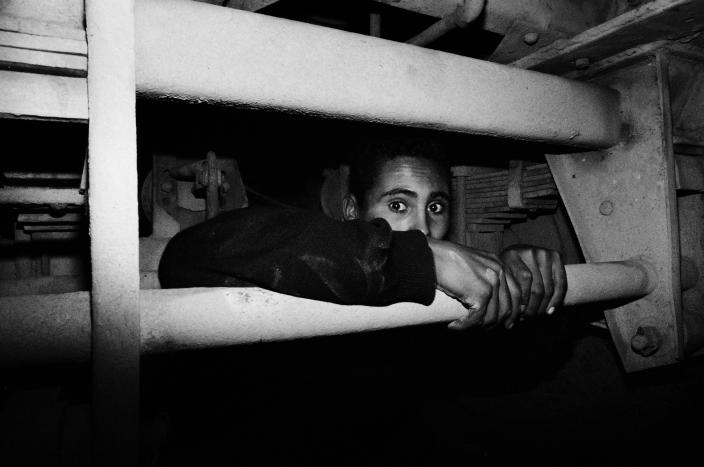 Mohammed, 16, hides under a truck in the port of Tangier, Morocco, in 2004. (Photo: José Colón/MeMo for Yahoo News)