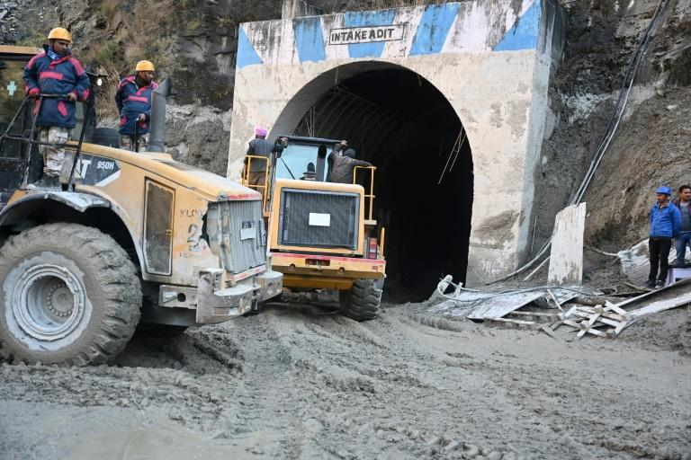 Bulldozers and rescue teams work at the entrance of a tunnel blocked with mud and debris after a flash flood -- some were lucky enough to escape
