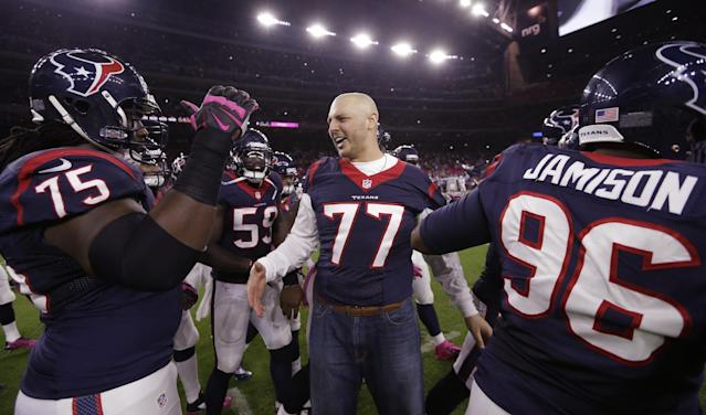 Houston Texans' David Quessenberry (77) who is battling cancer is acknowledged by teammates before an NFL football game against the Indianapolis Colts, Thursday, Oct. 9, 2014, in Houston. (AP Photo/David J. Phillip)