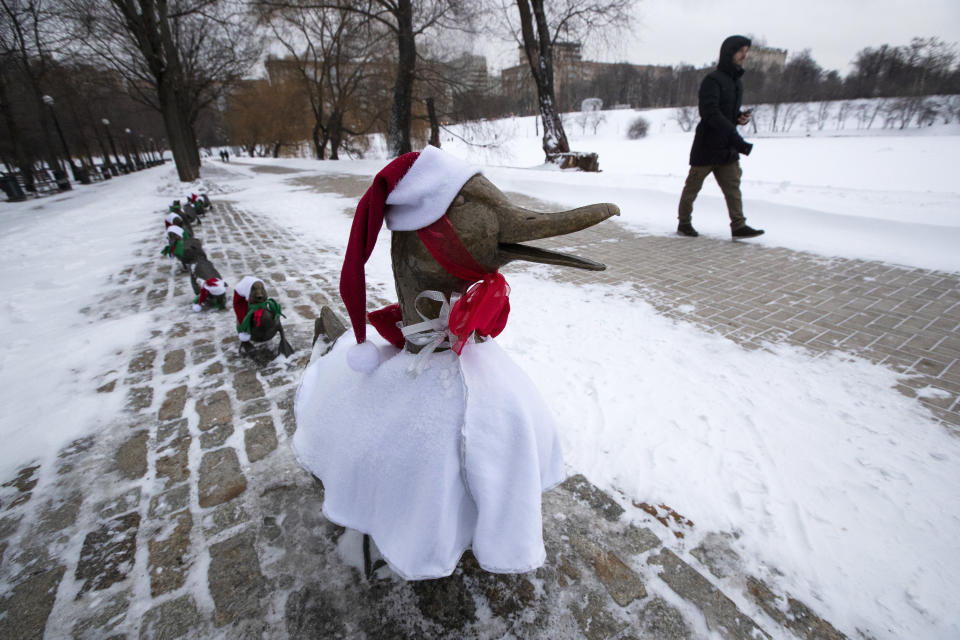 """A man passes a sculpture """"Make Way for Ducklings"""" dressed in Christmas costumes in Moscow's Novodevichy Park, Russia, Friday, Dec. 25, 2020. The copy of sculpture by Nancy Schon installed in the Boston Public Garden, U.S., became dressed in Santa Claus' hat every Catholic Christmas for several years like a tradition. Orthodox Christians celebrate Christmas on Jan. 7, in accordance with the Julian calendar. (AP Photo/Pavel Golovkin)"""