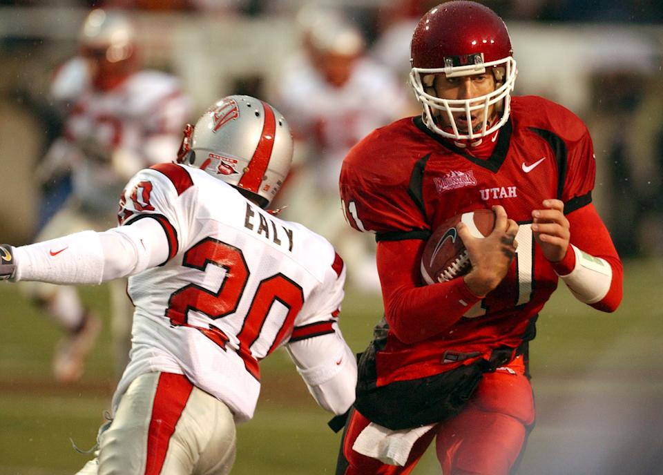 Utah quarterback Alex Smith (11) eludes the tackle by UNLVs Charles Ealy (20) enroute to a 70 yard touchdown during the first quarter Saturday, Oct. 23, 2004 at Rice - Eccles Stadium in Salt Lake City, Utah. (Photo by Ken Levine/Getty Images)