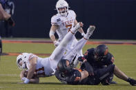 Texas quarterback Sam Ehlinger (11) is tackled by Oklahoma State's Brock Martin (40) and Thomas Harper (13) in the second half of an NCAA college football game in Stillwater, Okla., Saturday, Oct. 31, 2020. (AP Photo/Sue Ogrocki)