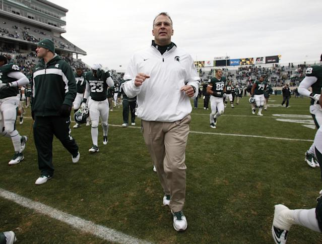 FILE - In this Nov. 19, 2011, file photo, Michigan State defensive coordinator Pat Narduzzi, center, jogs off the field following the Spartans 55-3 win over Indiana in an NCAA college football game in East Lansing, Mich. Narduzzi won the annual Broyles Award on Tuesday, Dec. 10, 2013, given to the top college assistant coach. (AP Photo/Al Goldis, File)