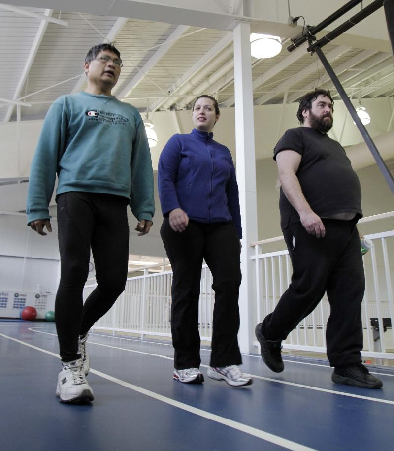 In this photo taken Tuesday Feb. 7, 2012 Health Mentor Brenda Beffum, center walks with Andy Parsley, left, and Craig Carey at the YMCA,  in Keene, N.H. Parsley and Carey are part of a fitness program for people with serious mental illness. (AP Photo/Jim Cole)