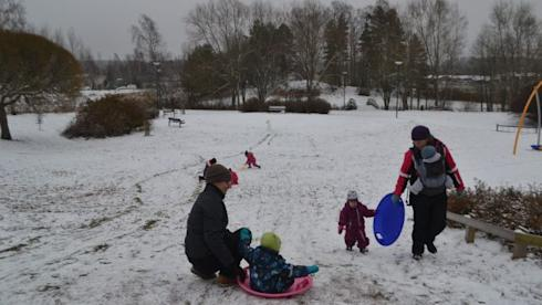 Parents play with their kids in the snow