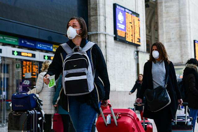 Passengers at Milano Centrale train station in Milan, Italy, wear protective respiratory masks as restrictive measures are taken to contain the outbreak of the new coronavirus. (PA)