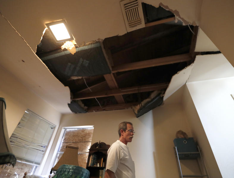 Kent Heap stands with a crumbling ceiling inside of his sister, Carol Goff's home, as people continued to sift through their damaged homes on Bridgeland Lane in Houston, Sunday, Jan. 26, 2020, after the Watson Grinding Manufacturing explosion early Friday morning.  (Karen Warren/Houston Chronicle via AP)