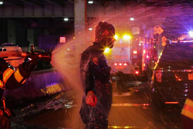 <p>A FDNY diver is sprayed with water after attending a call of a helicopter crash in the East River on March 11, 2018 in New York City. (Photo: Eduardo Munoz Alvarez/Getty Images) </p>