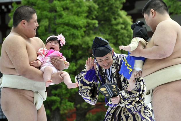 """Student sumo wrestlers carry crying babies during the """"Baby-cry Sumo"""" competition at Tokyo's Sensoji temple on April 30, 2011.  Some 50 babies aged under one participated in the annual baby crying contest. Japanese parents believe that sumo wrestlers can help make babies cry out a wish to grow up with good health.   AFP PHOTO/Yoshikazu TSUNO"""