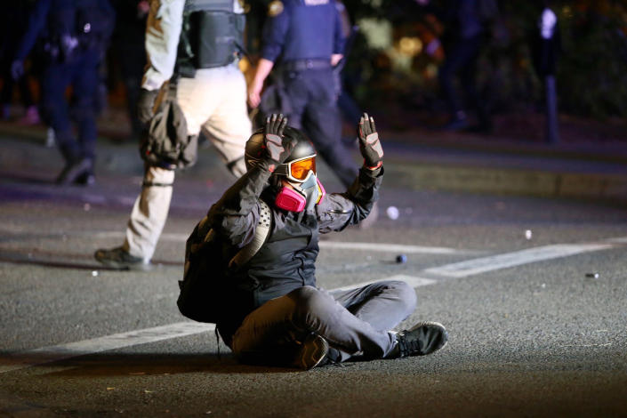 Protesters and police clash during a demonstration, early Thursday, Aug. 13, 2020, in downtown Portland. Officers used tear gas to break up the crowd of several hundred people who gathered near the Mark O. Hatfield U.S. Courthouse, the neighboring Multnomah County Justice Center and a nearby police precinct station. (Sean Meagher/The Oregonian via AP)