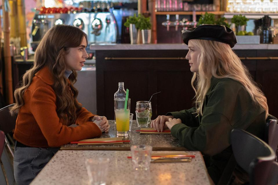 Emily (Lily Collins) and Camille (Camille Razat) in Emily in Paris, not talking about how Emily's harboring feelings for Camille's boyfriend