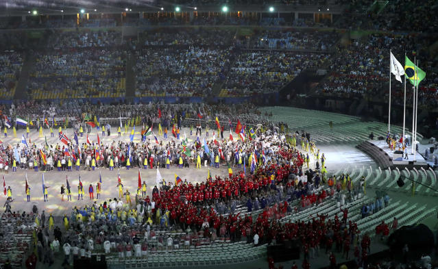 <p>Athletes from Canada come into the arena to take their seats, as the Olympics flag and the Brazilian national flag is seen at one end of the arena during the 2016 Rio Olympics closing ceremony on August 21, 2016. (REUTERS/Yves Herman) </p>