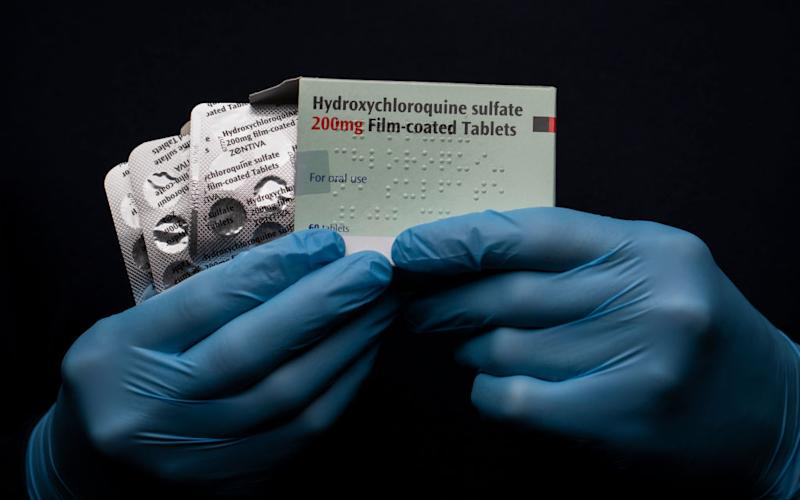 A pack of Hydroxychloroquine Sulfate medication is held up.