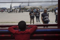 A little boy looks at police from aboard the Ocean Viking in the Mediterranean Sea, Tuesday, Sept. 24, 2019. He was among 182 people aboard the Ocean Viking rescued in the Mediterranean Sea north of Libya. (AP Photo/Renata Brito
