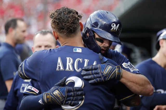 Milwaukee Brewers' Mike Moustakas gets a hug from teammate Orlando Arcia (3) after hitting a three-run home run during the first inning of a baseball game against the St. Louis Cardinals Wednesday, Aug. 21, 2019, in St. Louis. (AP Photo/Jeff Roberson)