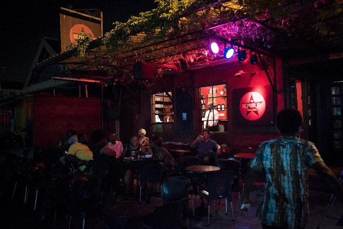Customers sit outside the Republic Bar & Grill, one of the most well-known pubs in Accra and popular for its cocktails (AFP Photo/CRISTINA ALDEHUELA)