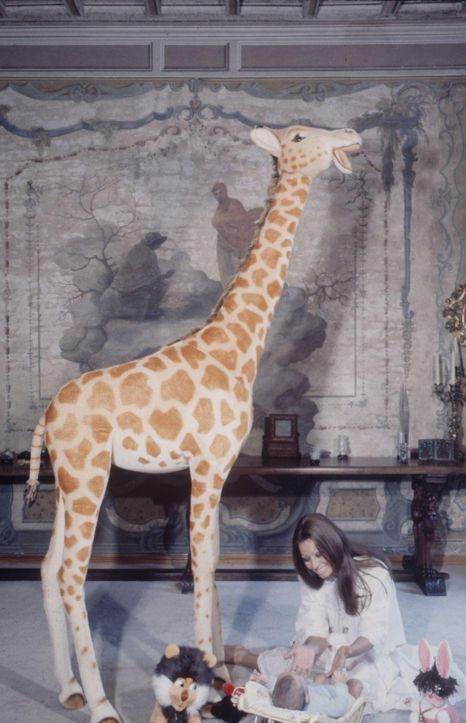 <p>A stuffed giraffe towers over the Italian actress, while she plays with her newborn son, Carlo Ponti, Jr., in 1969. Sophia raised her son in a Roman countryside villa she shared with her husband, director Carlo Ponti. </p>