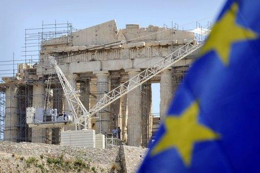 Workers on scaffolding work  in front of the Parthenon Temple at the Acropolis archaeological site in Athens