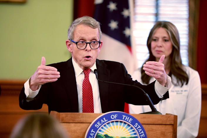 Ohio Gov. Mike DeWine makes a point, as State Health Director Dr. Amy Acton looks on, at a mid-March coronavirus briefing.