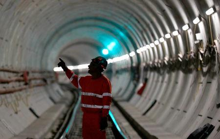FILE PHOTO: A worker stands on the railway track in a tunnel of the Crossrail project in Stepney, east London, Britain, November 16, 2016. REUTERS/Stefan Wermuth/File Photo