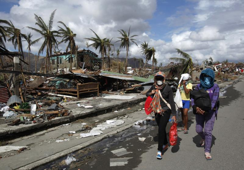 Residents don masks as they walk past damaged houses in the aftermath of super typhoon Haiyan in Tacloban