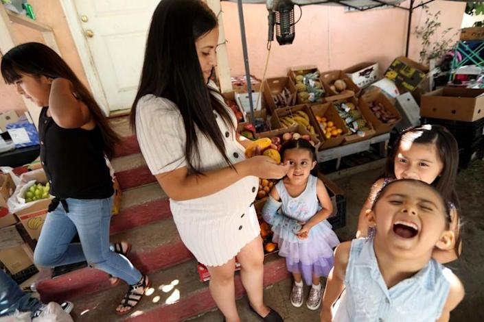"Maria Reyes, second from left, spends time with her daughters Marilyn, 9, from left, Darlene, 4, Sophia, 6, and Leilani, 5, right, near their home in Los Angeles on July 27. <span class=""copyright"">(Genaro Molina / Los Angeles Times)</span>"