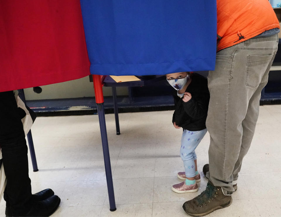 A child peeks out from the voting booth as voters mark their ballots during early in-person voting, Thursday, Oct. 29, 2020, in Cambridge, Mass. (AP Photo/Elise Amendola)