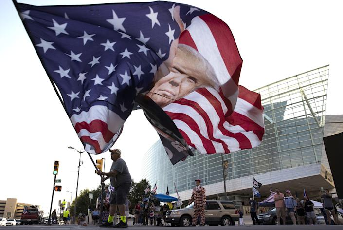 Trump supporter Randall Thom waves a giant Trump flag to passing cars outside the BOK Center June 18, 2020 in Tulsa, Oklahoma. Trump is scheduled to hold his first political rally since the start of the coronavirus pandemic at the BOK Center on Saturday while infection rates in the state of Oklahoma continue to rise.