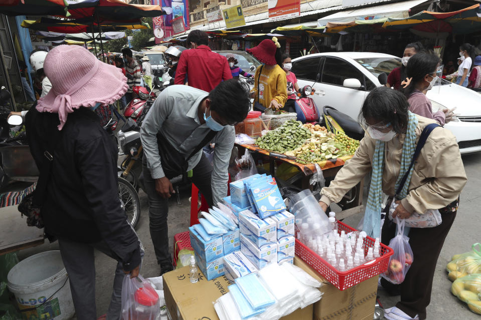 A customer, right, wears a protective face mask to prevent the spread of the coronavirus, buys items at a local market outside Phnom Penh, Cambodia, Saturday, April 10, 2021. (AP Photo/Heng Sinith)