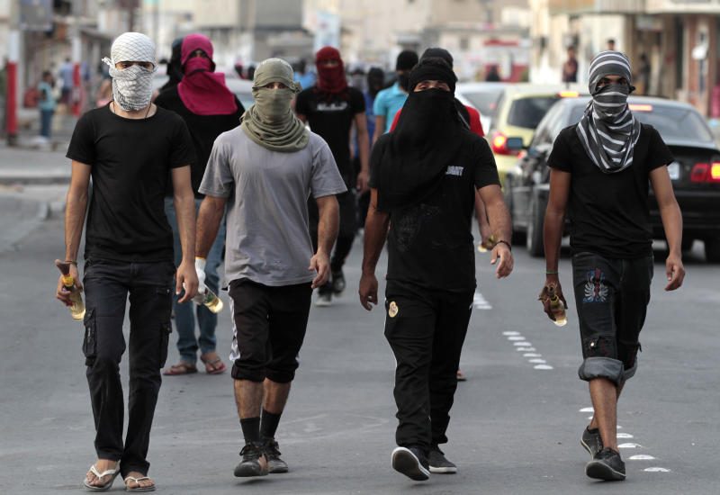 Masked Bahraini anti-government protesters carry petrol bombs ahead of a march in Malkiya, Bahrain, on Sunday, Oct. 28, 2012, where marchers were calling for freedom for political prisoners and honoring those killed in the uprising from Bahrain's western villages. Youths with petrol bombs walked ahead and behind the marchers as lookouts for any riot police who might approach to disperse the gathering. Clashes between protesters and police erupted as the march was ending. (AP Photo/Hasan Jamali)