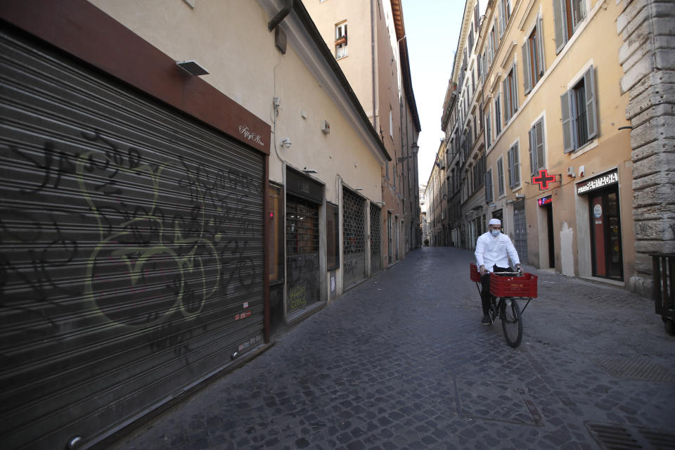 FILE - In this March 15, 2021, file photo, a man wearing a face mask to curb the spread of COVID-19, pedals past closed shops in downtown Rome. Optimism is spreading in the U.S. as COVID-19 deaths plummet and states ease restrictions and open vaccinations to younger adults. But across Europe, dread is setting in with another wave of infections that is closing schools and cafes and bringing new lockdowns. (AP Photo/Alessandra Tarantino, File)