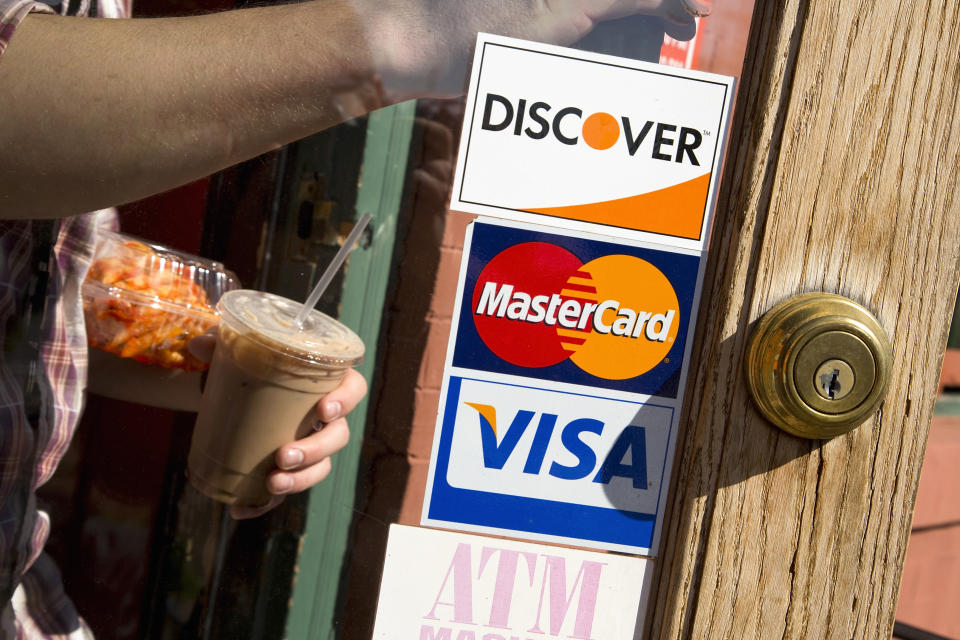 A coffee shop displays signs for Visa, MasterCard and Discover, in Washington, May 1, 2013. This logo has been updated and is no longer in use.  REUTERS/Jonathan Ernst    (UNITED STATES - Tags: BUSINESS)