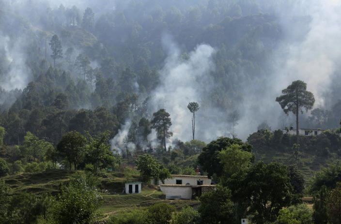 FILE- In this May 13, 2017, file photo, smoke rises from a mortar shell fired from the Pakistan side of the border in a civilian area at Bhawani village at Nowshera sector, along the highly militarized Line of Control that divides the region between India and Pakistan. The machine guns peeking over parapets of small, sandbagged concrete bunkers, and heavy artillery cannons dug deep into Himalayan Kashmir's rugged terrain, have fallen silent. The Line of Control, a highly militarized de facto border that divides the disputed region between the two nuclear-armed rivals India and Pakistan, and a site of hundreds of deaths, is unusually quiet after the two South Asian neighbors agreed in February 2021 to reaffirm their 2003 cease-fire accord. (AP Photo/Channi Anand, File)