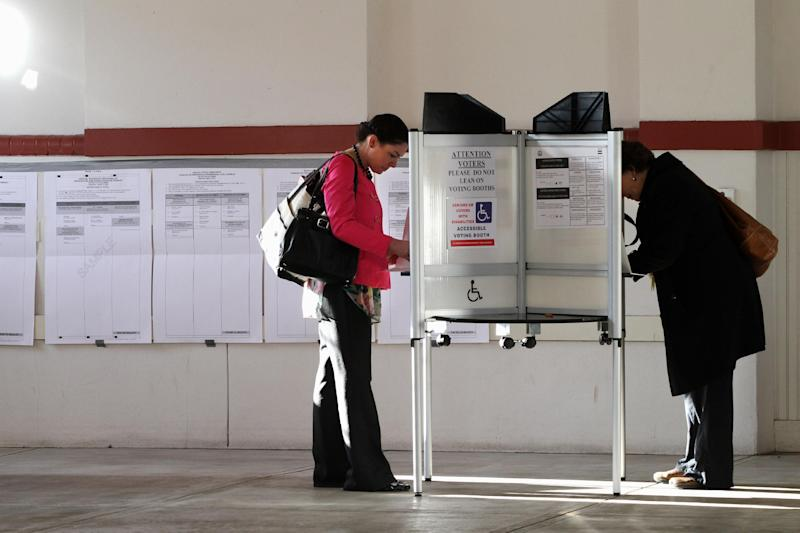 Leslie McDermott of Washington, left, votes in the District of Columbia primary election at Eastern Market in Washington, Tuesday, April 3, 2012. (AP Photo/Jacquelyn Martin)