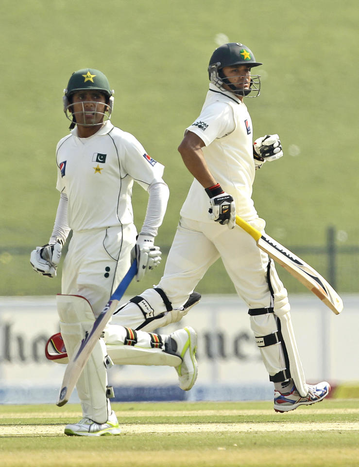 Pakistan's Azhar Ali, right, and teammate Adnan Akmal run between the wickets during the fourth day of the second cricket test match of a three match series between England and Pakistan at Zayed Cricket Stadium in Abu Dhabi, United Arab Emirates, Saturday, Jan. 28, 2012. (AP Photo/Hassan Ammar)