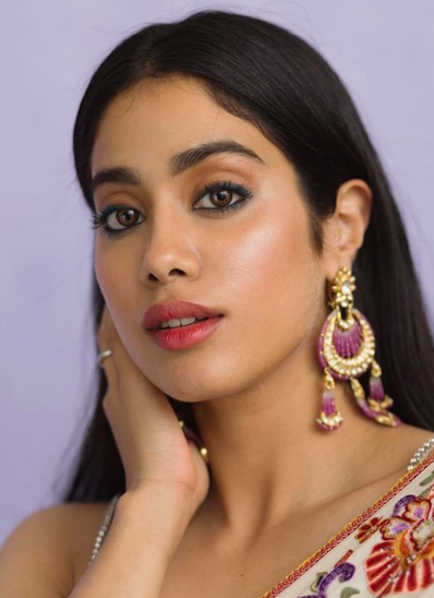 """""""The tender temptress, Jhanvi with her innocent face, liquid eyes and pretty pout can melt hearts and concrete easily! The soft pencilled eyeliner, dewy skin and elegantly defined lips are a sure winner for this innocent Indian temptress. <strong>Get this look </strong>with a primer, liquid highlighter under your foundation blended seamlessly into the skin. Then contour, highlight and blush. Use the soft peach eyeshadow from the <a href=""""https://fave.co/31DnyOS"""" rel=""""nofollow noopener"""" target=""""_blank"""" data-ylk=""""slk:Manish Malhotra 9 in 1 Eyeshadow Palette - Soirée"""" class=""""link rapid-noclick-resp"""">Manish Malhotra 9 in 1 Eyeshadow Palette - Soirée</a>, eye pencils in black and brown gently blended around the eyes for that innocent fire. Finish your look with mascara, a soft nude pink lipstick, and slay!"""""""