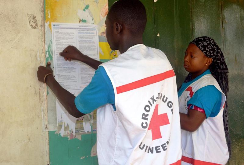 Members of the Guinean Red Cross display information concerning the Ebola virus during an awareness campaign on April 11, 2014 in Conakry