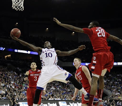 Kansas' Tyshawn Taylor (10) goes for a layup against Detroit's LaMarcus Lowe (20), Ray McCallum (3) and Evan Bruinsma (33) in the first half of their NCAA tournament second-round college basketball game at CenturyLink Center in Omaha, Neb., Friday, March 16, 2012. (AP Photo/Nati Harnik)