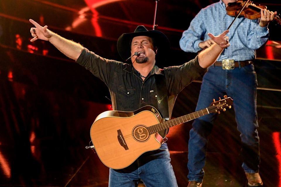 Garth Brooks, on stage with a fiddler, wears jeans and cowboy hat with his guitar slung over his shoulders.