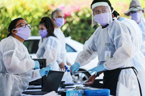 PHOTO: Healthcare workers facilitate tests at a drive-in COVID-19 testing center at M.T.O. Shahmaghsoudi School of Islamic Sufism on Aug. 11, 2020, in Los Angeles. (Mario Tama/Getty Images)