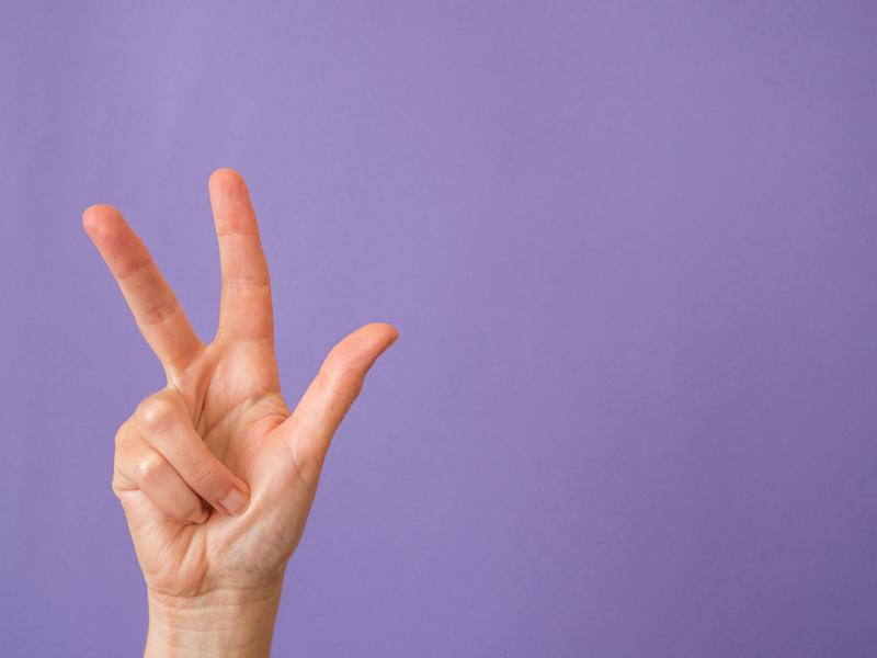 Hand with three fingers raised on purple background and copy space