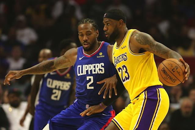 "Lakers forward LeBron James drives against Clippers forward Kawhi Leonard during a game earlier this season, which appears to be on track to resume this summer. <span class=""copyright"">(Robert Gauthier / Los Angeles Times)</span>"