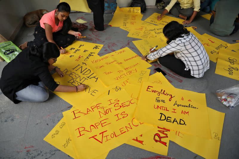 Students write placards before a protest against the alleged rape and murder of a 27-year-old woman, in Kolkata
